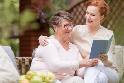 Cheerful senior women with her tender caretaker reading a book together while relaxing outside.