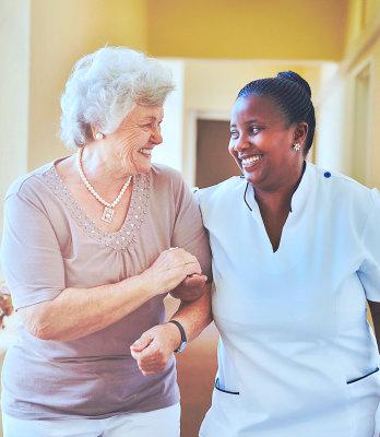an elder and a caregiver smiling